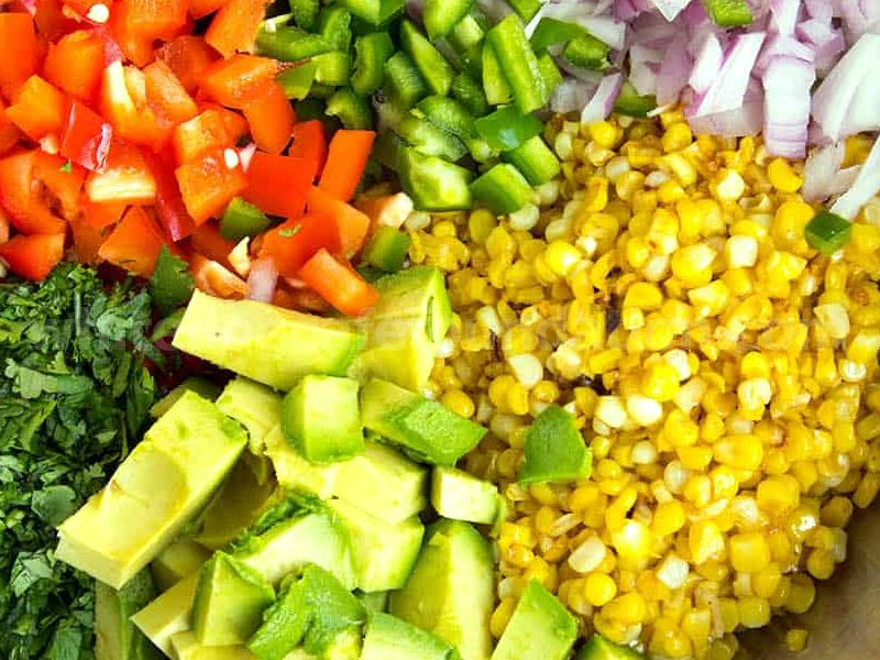 Elotes salad ingredients in a bowl